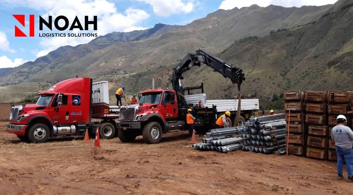 Dos camiones de carga descargando vigas de metal
