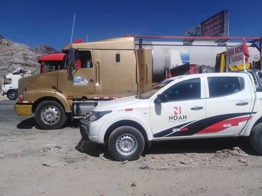 camioneta pick up de noah logistica estacionada al costado de un camion